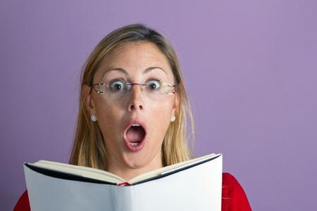 femme bouche ouverte: Surpris jeune femme lisant un livre Banque d'images