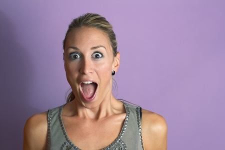Surprised young sexy woman in pink background