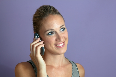 Portrait of an attractive and smiling woman talking on mobile phone in purple background photo