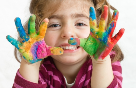 Portrait of a beautiful preschool girl with painted hands in background white photo