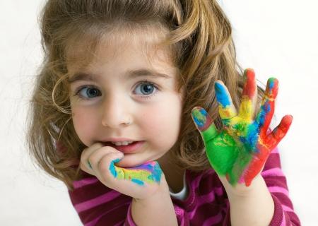 good bye: Preschool girl waving hello goodbye with her hands painted Stock Photo