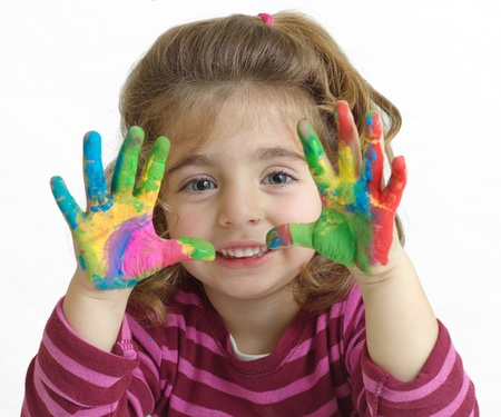 Portrait of a beautiful preschool girl with painted hands in background white
