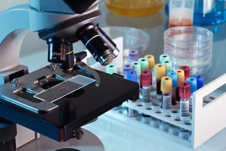 genetica: Workbench laboratorio banca del sangue con un microscopio e provette con i campioni dei pazienti Archivio Fotografico