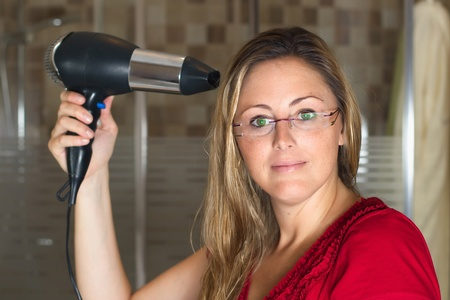 blow drier: Portrait of young woman using hairdryer in the bathroom Stock Photo