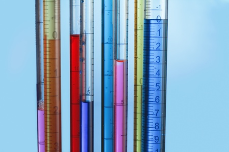 calibrated: collection of calibrated pipettes filled with colored fluid on a blue background