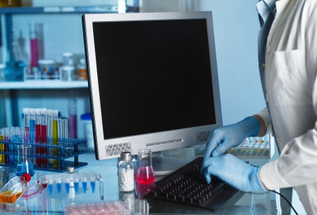 Scientist working at lab with computer photo