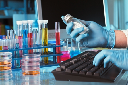 pharmaceutical research: research chemist with a bottle of pills with logging data in the computer laboratory
