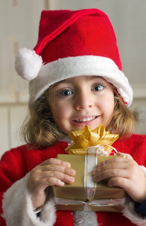 '5 december': Little Girl at home with a Christmas gift in hands