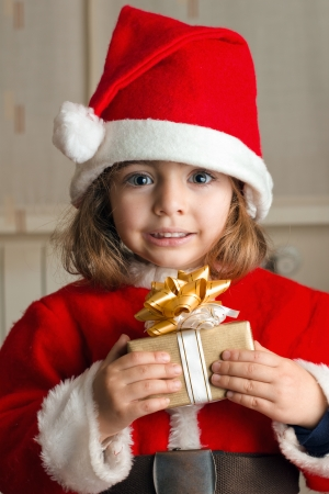 Little Girl at home with a Christmas present in hands photo