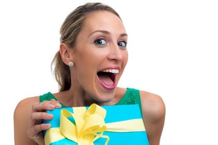 Donna divertente in possesso di un regalo avvolto in confezione blu, isolato su bianco