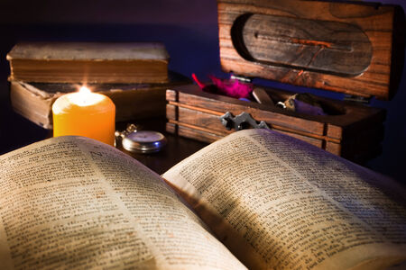 An old desk with an open book illuminated by a candle and several more objects in the background photo