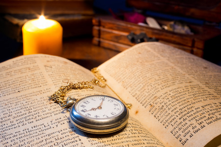 An open old book with  pocket-watch antique illuminated by candlelight and various ancient objects in background Stock Photo