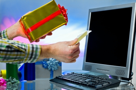 Male hands using computer and holding box gift and credit card for online payment photo