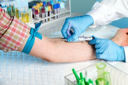 Laboratorium met verpleegster nemen van een bloedmonster van de patiënt, op de achtergrond monsters bloed en urine buizen