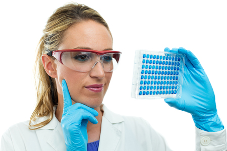laboratory woman examining a 96 well microplate in hand photo