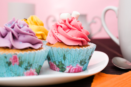 vanilla cupcake: various cupcakes on a plate on pink background