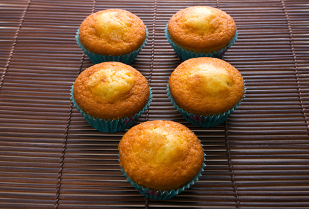 cupcakes isolated: table with recent homemade golden muffins from the oven