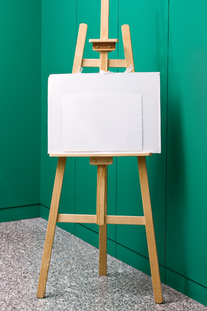 Wooden easel with blank canvas in front of a green wall photo