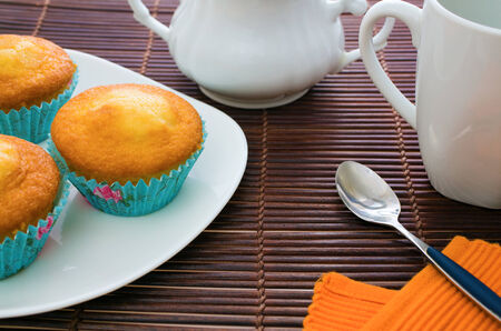 various muffins on a plate with tea set photo