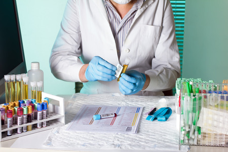 traceability: laboratory technician holding and labeling sample tubes urine and blood for coding traceability Stock Photo