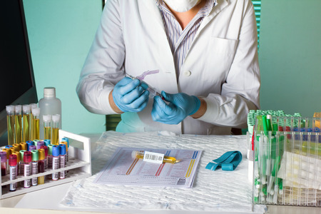 lab worker taking a tube and on the laboratory bench instrumental Stock Photo
