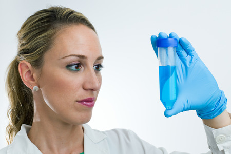 portrait of young scientist studying sample tube photo