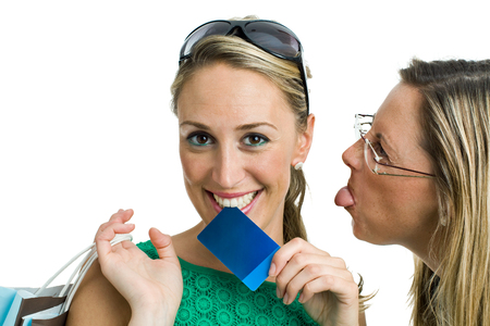 envy: two young shopping, one woman sticking out her tongue and making fun of envy to happy friend   envy on purchases