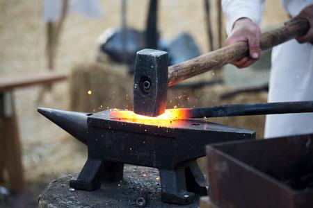 smid werkt metaal met hamer op het aambeeld in de smidse Stockfoto