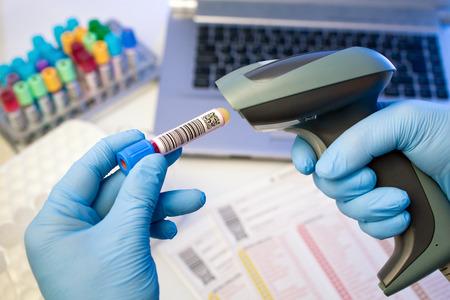 혈액 은행의 실험실에서 생체 시료 관에 바코드를 스캔 기술자의 손
