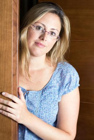 Happy casual girl woman opening her house door photo