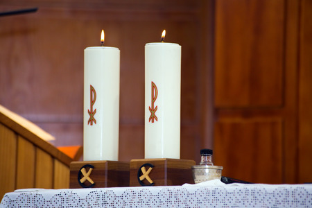 two candles lighted on the altar of the church during the celebration of the Mass photo