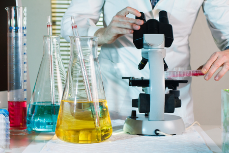 reagent: worktable research lab with a scientist examining a sample under the microscope Stock Photo