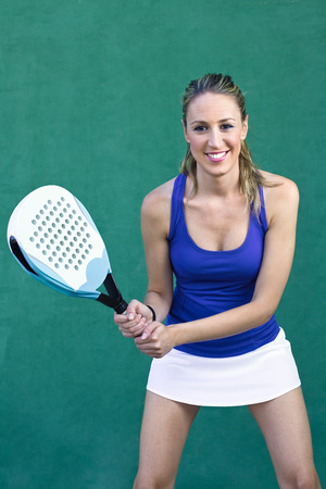 young woman playing paddleball tennis on paddle court wall green background photo