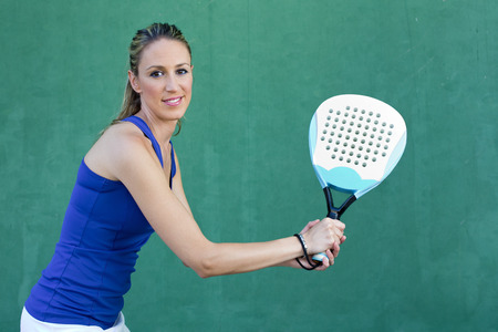 young woman playing paddleball tennis on paddle court waiting ball in wall green background photo