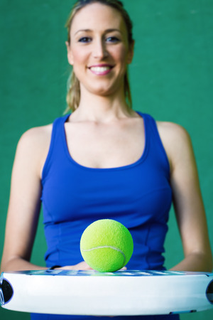 young woman holding paddleball tennis on paddle court waiting ball in wall green background photo