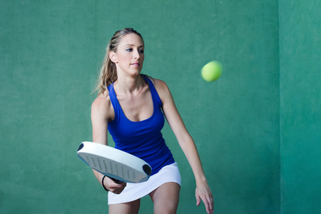 young woman playing serving ball paddleball tennis on paddle court in wall green background