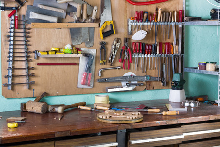 work table of a carpenter with many tools hanging in the background