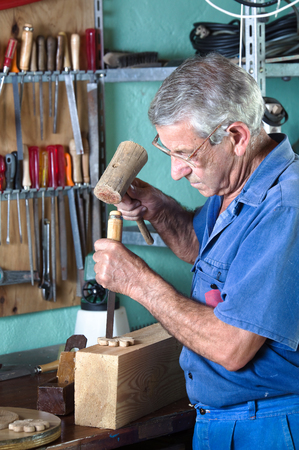 carpenter in the workshop handling a chisel and a hammer on a piece of wood photo