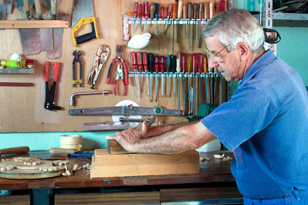 portrait of a carpenter planing on a piece of wood at work in the workshop photo