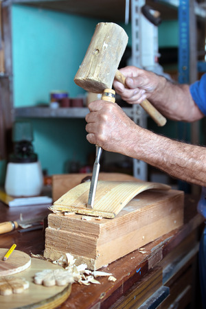 workbench: hands of carpenter in workshop carving on workbench a piece of wood with chisel and a hammer
