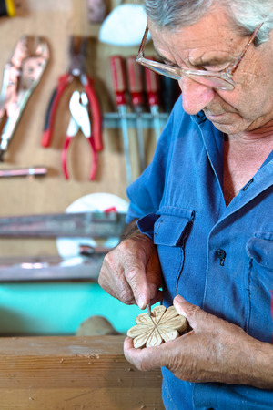 hands of craftsman in workshop manually sanding on workbench a decorative figura of wood with carpenters tool in hands  cabinetmaker modeling a decorative piece of wood Stock Photo