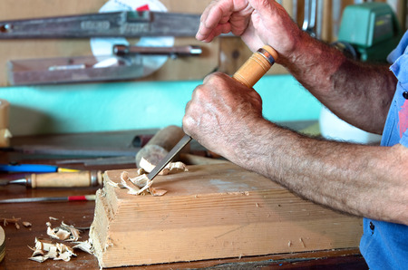 bussiness time: hands of craftsman on workbench modeling manually a decorative figure of wood with carpenters tool in hands  cabinetmaker carving a piece of wood with chisel and using his hand as a hammer