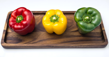 three Bell Peppers of colors shown in tray and isolated on white background  three Bell Peppers, red, yellow and green photo