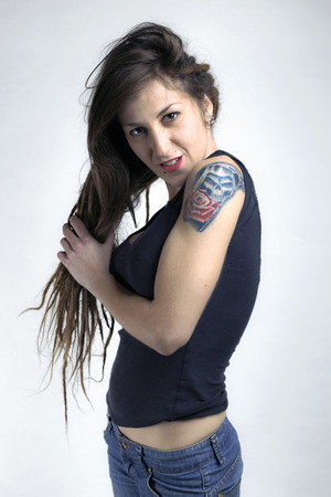 A young female with arm tattoo holding her long hair in white wall portrait of girl with tatto in white wall  tattoo of a rose and skull in her arm