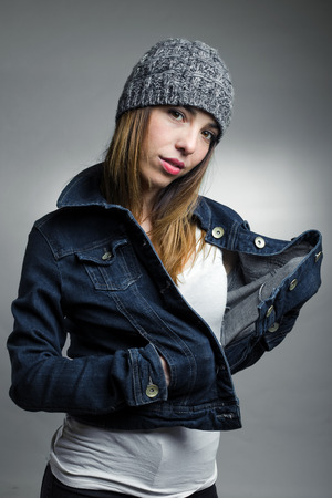 denim jacket: beautiful Caucasian teenage girl fashionable in denim jacket and hat isolated at gray background  fashionable girl in denim jacket