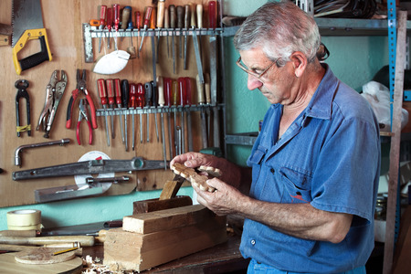 manual test equipment: horizontal portrait of carpenter examining handmade pieces of wood workshop  work cabinetmaker looking handcrafted wooden pieces in garage at home