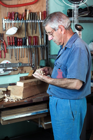 manual test equipment: vertical portrait of carpenter examining handmade pieces of wood workshop  work cabinetmaker looking handcrafted wooden pieces finished in garage at home Stock Photo