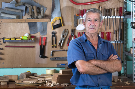 Portrait of a worker in work clothes in front of workbench tools  Portrait of man at work in workshop in garage at home Stock Photo