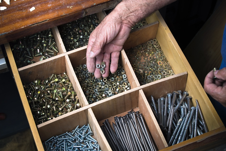 Desk drawer of a cabinet maker working with several compartments with nuts, screws, nails, bolts / Screws drawer 免版税图像