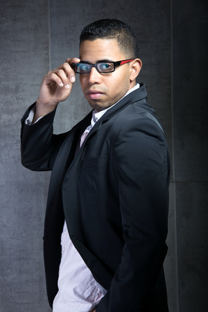 backwards: young man latin with fashionable glasses looking back wearing a suit in front of a dark gray wall  Trendy Businessman young looking backwards Stock Photo
